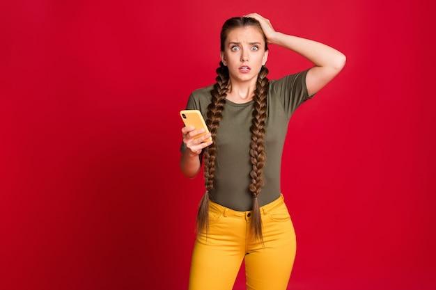 Foto der lustigen dame telefon hände halten arm auf dem kopf nicht glauben augen episch scheitern neues startup-projekt tragen lässig gelbe hosen grün t-shirt isoliert rote farbe hintergrund