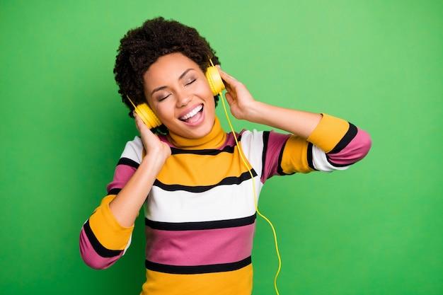 Foto der lustigen dunklen haut dame halten moderne technologie kopfhörer hören neue beliebte lieder augen geschlossen tragen lässig gestreiften pullover