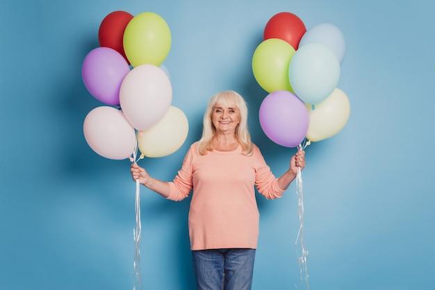 Foto der lustigen frau hält viele luftballons im rosa pullover auf blauem hintergrund