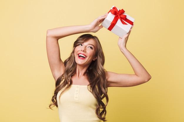 Foto der lustigen freudigen frau 20s mit langen braunen haaren, die lächeln und geschenkbox mit bogen über ihrem kopf gewickelt halten, lokalisiert über gelbem hintergrund