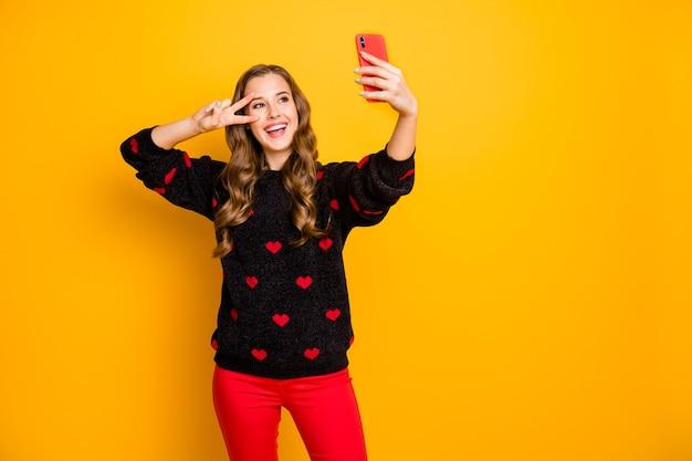 Foto der lustigen hübschen dame halten telefonhände, die lustige energetische selfies nehmen, die v-zeichen nahe augen tragen herzen muster pullover rote hose zeigen