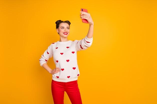 Foto der lustigen hübschen dame halten telefonhände, die lustige selfies nehmen, die skypefreunde sprechen, tragen herzmuster weißen pullover