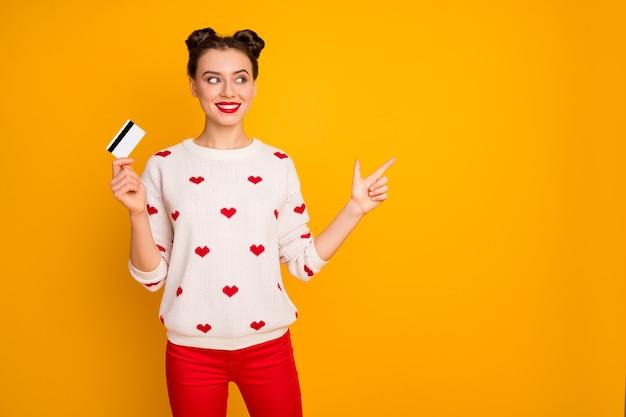 Foto der lustigen interessierten dame halten plastikkreditkarte anzeigen finger leeren raum empfehlen schnelle zahlung weg tragen herzen muster pullover