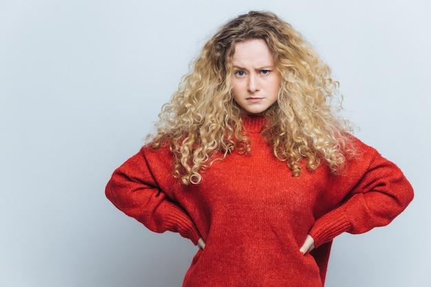 Foto der missfallenen verärgerten frau mit dem gelockten haar, hält hände auf taille