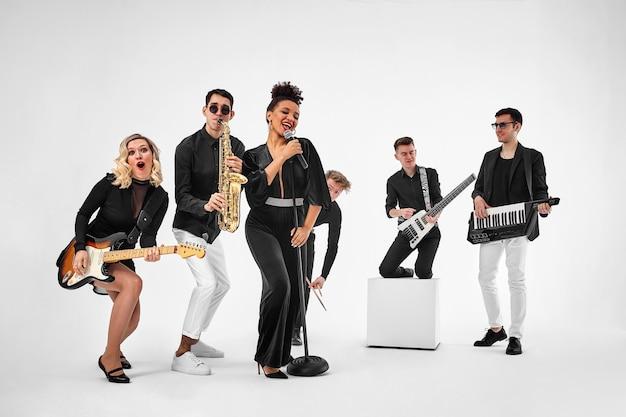 Foto der multiethnischen musikband im studio musiker und solistin, die über weißem hintergrund aufwerfen