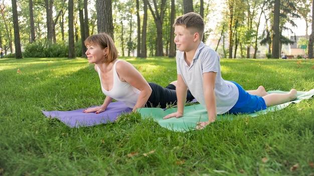Foto der mutter mit ihrem sohn im teenageralter, der yoga asana auf gras im park praktiziert. familie macht fitness und sport im wald?