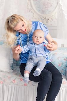 Foto der mutter spielt mit dem baby im kinderzimmer und lächelt