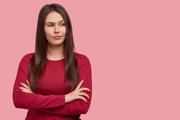 Foto der nachdenklichen brünetten jungen frau mit dunklem haar, hält arme verschränkt, denkt an etwas im sinn, trägt roten pullover, steht vor rosa hintergrund. menschen