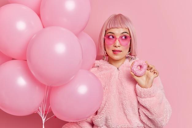 Foto der nachdenklichen entzückenden jungen frau mit dem östlichen aussehen rosiges haar beißt lippen hält köstliche aufgeblasene donutballons