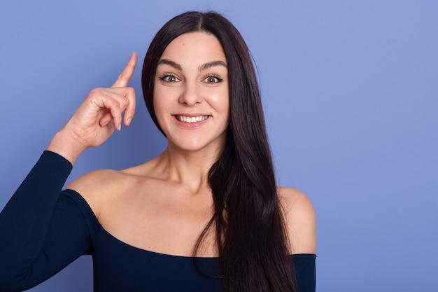 Foto der netten lächelnden dame, die kleid trägt, das ihren finger im eureka-zeichen zeigt, mit großer innovativer idee, problemlösung habend.