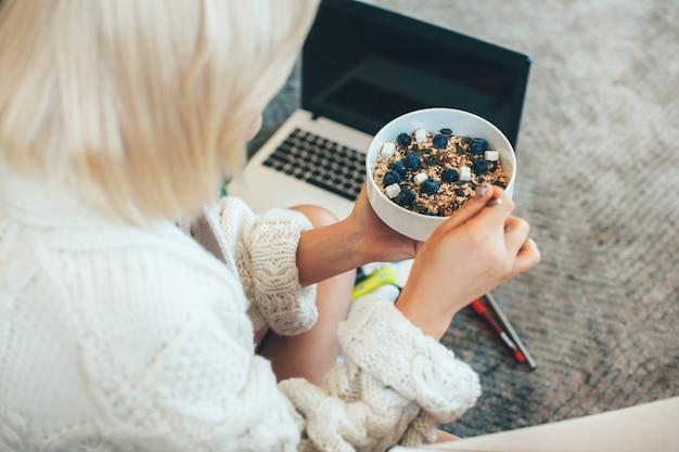 Foto der oberen ansicht einer blonden dame, die müsli während der arbeit am laptop auf dem boden isst