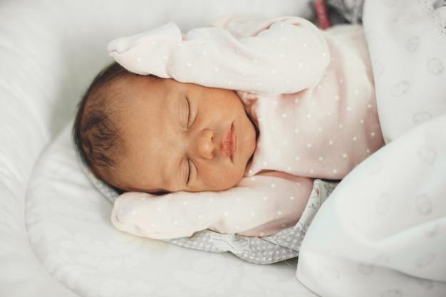 Foto der oberen ansicht eines neugeborenen babys schlafend im bett, das niedliche kleidung trägt