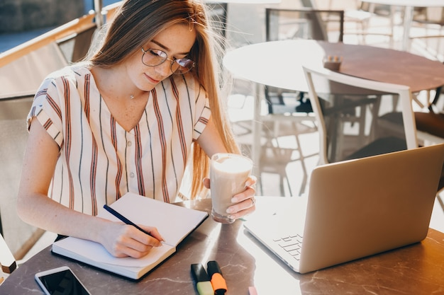 Foto der oberen seite eines netten mädchens, das in einem heft arbeitet und mit einer tasse kaffee am computer sitzt