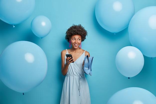 Foto der positiven afroamerikanerin im modischen kleid, nimmt schuhe mit hohen absätzen passend zum outfit, tippt nachrichten auf dem smartphone und macht einen termin für ein treffen, hat gute laune im urlaub