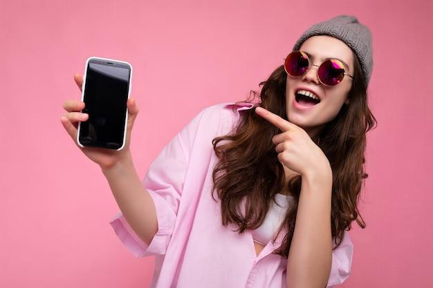 Foto der positiven attraktiven jungen brünetten frau, die stilvollen rosa hemd grauen hut und bunte trägt
