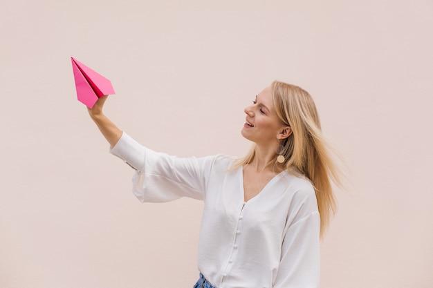 Foto der positiven blonden frau halten handpapierflugzeug, das über lokalisiertem beige hintergrund steht.