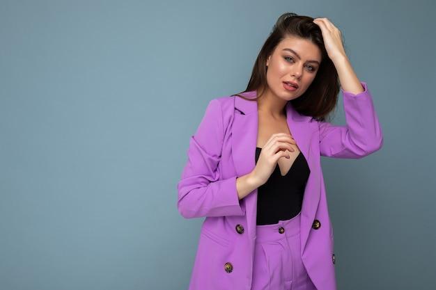 Foto der positiven jungen geschäftsfrau des langen haares brunette, die purpurroten anzug lokalisiert auf blauem hintergrund trägt. platz kopieren