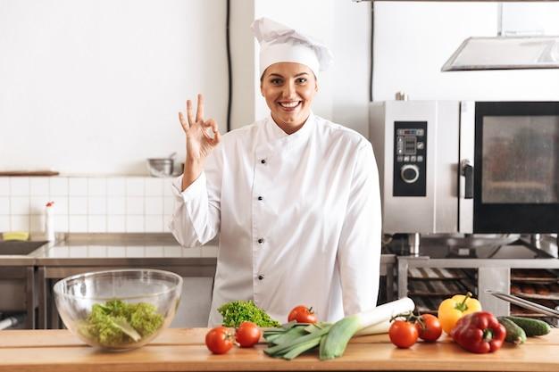Foto der professionellen köchin, die weiße einheitliche kochmahlzeit mit frischem gemüse trägt, in der küche am restaurant