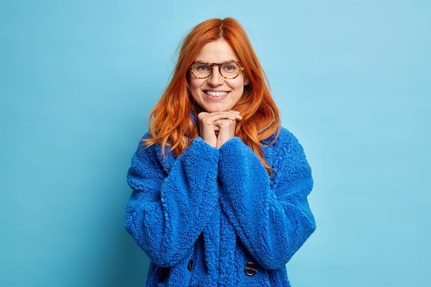Foto der reizenden europäischen ingwerfrau lächelt fröhlich und hält hände unter kinn trägt optische brille und warmen pelzmantel.