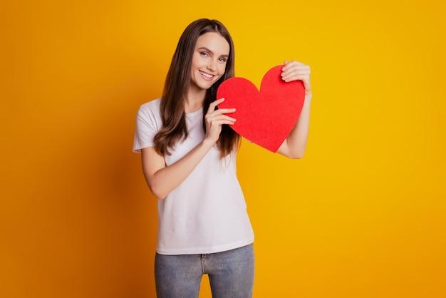 Foto der romantischen dame halten rotes papierherz tragen weißes t-shirt, das auf gelbem hintergrund posiert