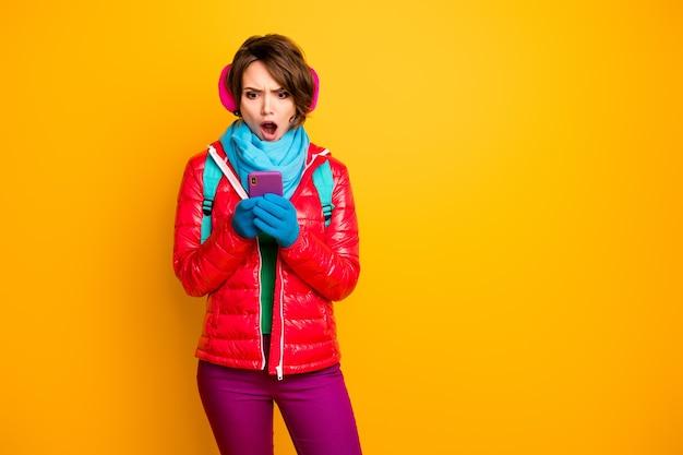 Foto der schockierten bloggerin dame gehen straße suchen telefon überprüfen anhänger schlechte nachrichten tragen lässig roten mantel blauen schal handschuhe ohrhüllen hosen