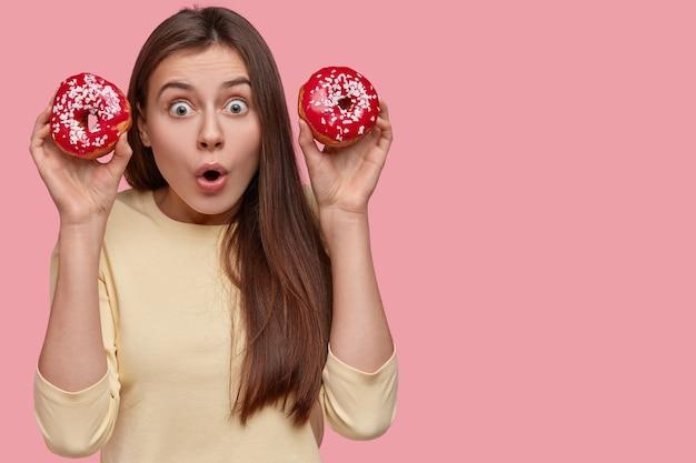 Foto der schockierten kaukasischen dame hält den atem an, trägt rote süße donuts