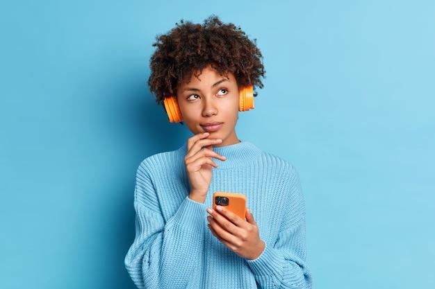 Foto der schönen afroamerikanischen frau hört musik mit smartphone und kopfhörer hat nachdenklichen ausdruck gekleidet in gestricktem jumpper gekleidet