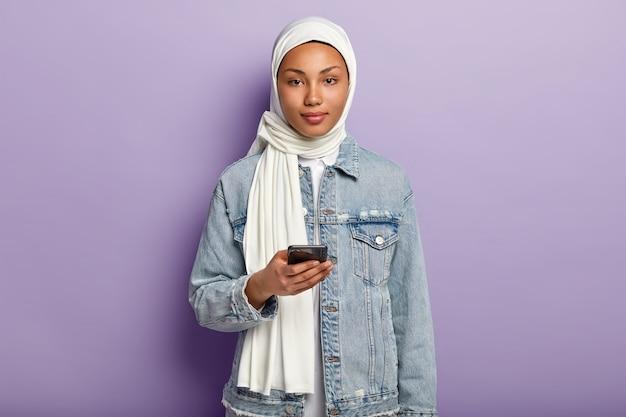 Foto der schönen arabischen frau mit dunkler gesunder haut, textnachricht auf modernem handy, liest kommentare unter post, trägt weiße hijab- und jeansmantelmodelle über lila wand. muslimische religion