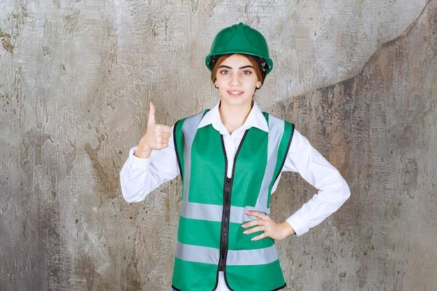 Foto der schönen architektin im grünen helm, die daumen hochgibt
