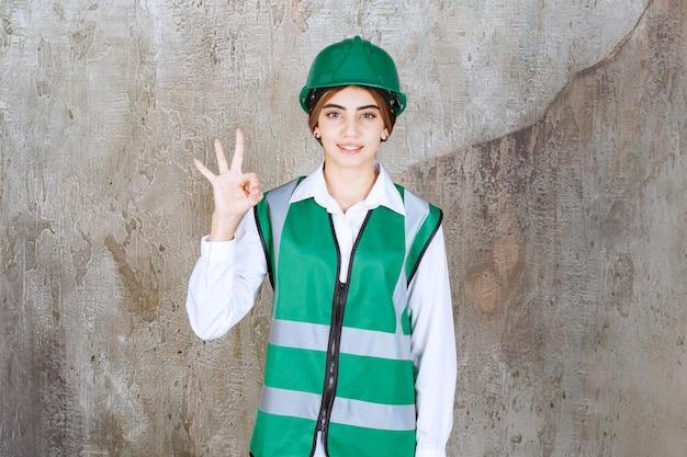 Foto der schönen architektin im grünen helm, die ein gutes zeichen gibt