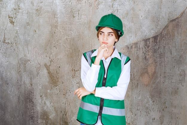 Foto der schönen architektin im grünen helm, die über marmor steht