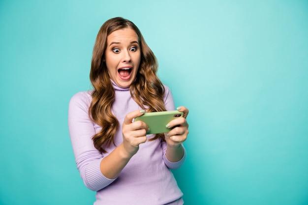 Foto der schönen dame halten grünen fall telefon offener mund erstaunliche drahtlose verbindung spielen videospiele tragen violetten pullover isoliert pastell blaugrün blaue farbe