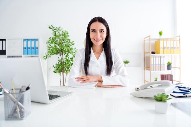 Foto der schönen doc lady freundliches lächeln tragen weißen laborkittel sitzen klinik drinnen