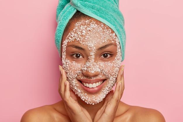 Foto der schönen dunkelhäutigen frau berührt wangen, sieht glücklich aus, lächelt breit, zeigt weiße zähne, kümmert sich um die persönliche hygiene, macht schönheitsbehandlung für das gesicht, trägt peeling-maske auf