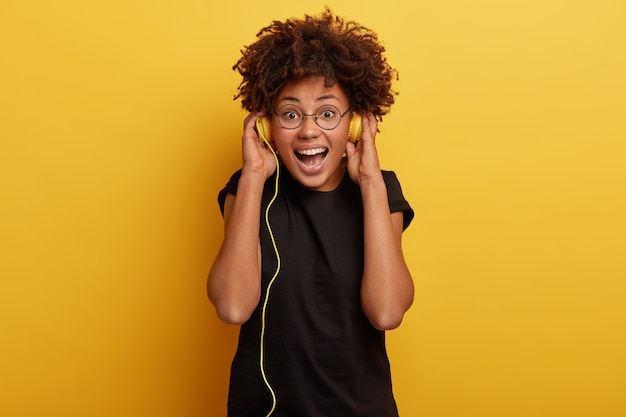 Foto der schönen dunkelhäutigen frau mit afro-frisur hat inspiration von musik, wählt schönen track