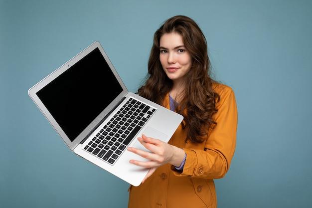 Foto der schönen ernsten glücklichen jungen frau, die computer-laptop hält, der kamera trägt, die gelbe jacke lokalisiert über blauem wandhintergrund betrachtet. ausgeschnitten