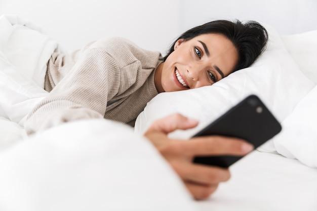 Foto der schönen frau 30s mit smartphone, während im bett mit weißer wäsche zu hause liegen