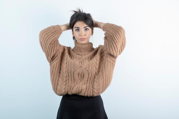 Foto der schönen frau im gestrickten pullover, der ihr haar auf weißem hintergrund hält.
