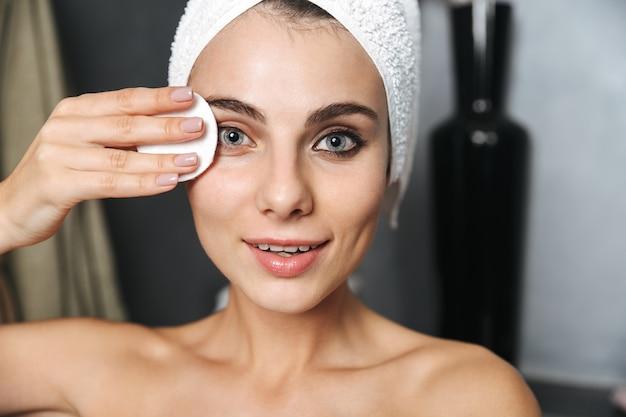 Foto der schönen frau mit handtuch auf kopf, das ihr gesicht reinigt und make-up mit wattepad entfernt
