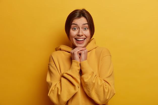 Foto der schönen fröhlichen frau schaut glücklich, hält hände unter kinn, verbringt freizeit in lustiger gesellschaft, lächelt zufrieden und sorglos, trägt hoodie, posiert gegen gelbe wand