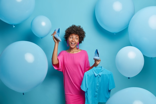 Foto der schönen fröhlichen frau wählt, was zu tragen, wählt blaues outfit für besondere anlässe, hält schuhe mit hohen absätzen und hemd auf kleiderbügel, posiert gegen dekorierte wand. kleiderkollektion