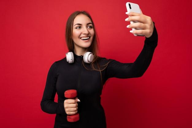 Foto der schönen fröhlichen jungen brünetten weiblichen person, die schwarze sportkleidung weiße kopfhörer trägt