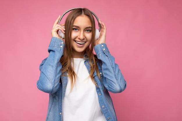 Foto der schönen glücklich lächelnden jungen blonden frau, die blaues jeanshemd und weißes t-shirt trägt
