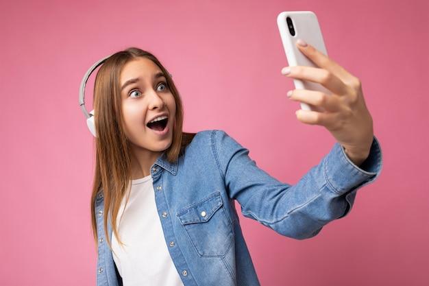 Foto der schönen glücklichen amaxed schockierten jungen blonden frau, die blaues jeanshemd und weißes t-shirt trägt