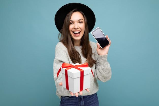 Foto der schönen glücklichen fröhlichen jungen brünetten frau lokalisiert über der blauen hintergrundwand, die trägt