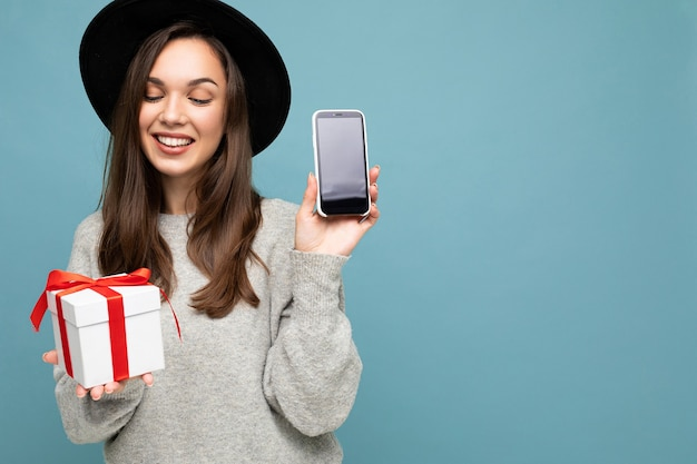 Foto der schönen glücklichen fröhlichen jungen brunettefrau lokalisiert über der blauen hintergrundwand, die trägt