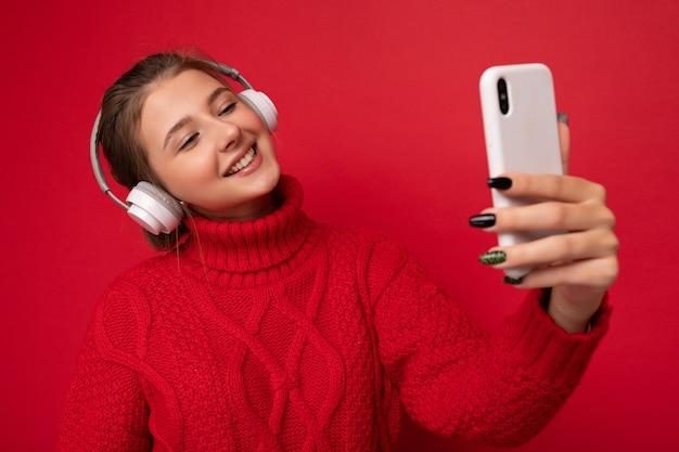 Foto der schönen glücklichen jungen brünetten frau mit rotem pullover isoliert über roter hintergrundwand