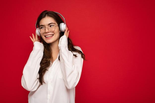 Foto der schönen glücklichen lächelnden jungen brünetten frau, die weißes hemd und optische brille trägt