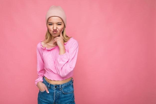 Foto der schönen glücklichen lustigen jungen blonden frau lokalisiert über rosa hintergrundwand, die trendy trägt