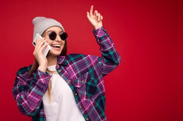 Foto der schönen glücklichen positiven jungen blonden frau, die purpurrotes hemd des hipsters und beiläufiges weiß trägt